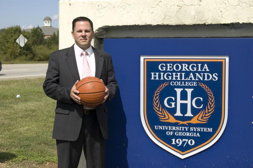 Highlands' new athletic director, Phillip Gaffney, standing next to the sign in front of the Floyd campus, plans to bring intercollegiate sports to Floyd, Cartersville and possibly other sites. Photo by Denise Perez Campos.