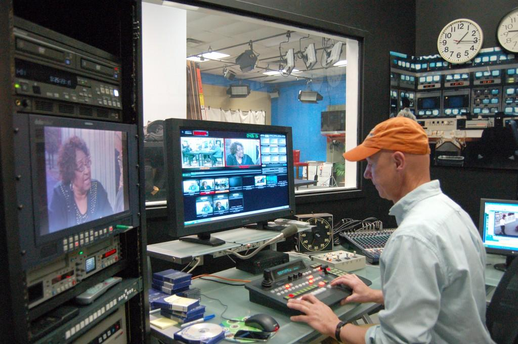 """Jeff Brown, director of digital media services, edits footage in the control room at GHTV during the taping of """"Community Watch."""" Photo by Derweatra Hammock."""