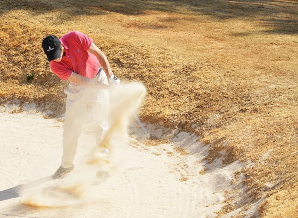 John Chandler, captain of the new GHC golf team swings his way out of a sand trap. Photo by Tatiana Smithson.