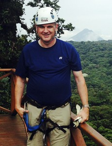 Mark Greger, associate professor of Spanish and faculty trip leader, prepares to zip line through a Costa Rican cloud forest with Arenal Volcano off in the distance. Contributed.