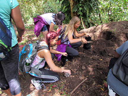 GHC students (from left) Kendall Sciascia, Karla Cruz and Rachel Allison help pack dirt in preparation for tree planting. Photo by Taylor Barton