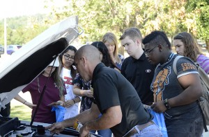 Bryce Wood of Jim's Tires demonstrates to GHC students how to locate the car battery and attach jumper cables. Photo by Xavier Freeman