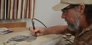 Billy Morris uses a tool to scrape away rock and expose the fossil underneath. The fossil Morris is preparing above was so well preserved that the fossil still has skin on it. Photo by Catie Sullivan