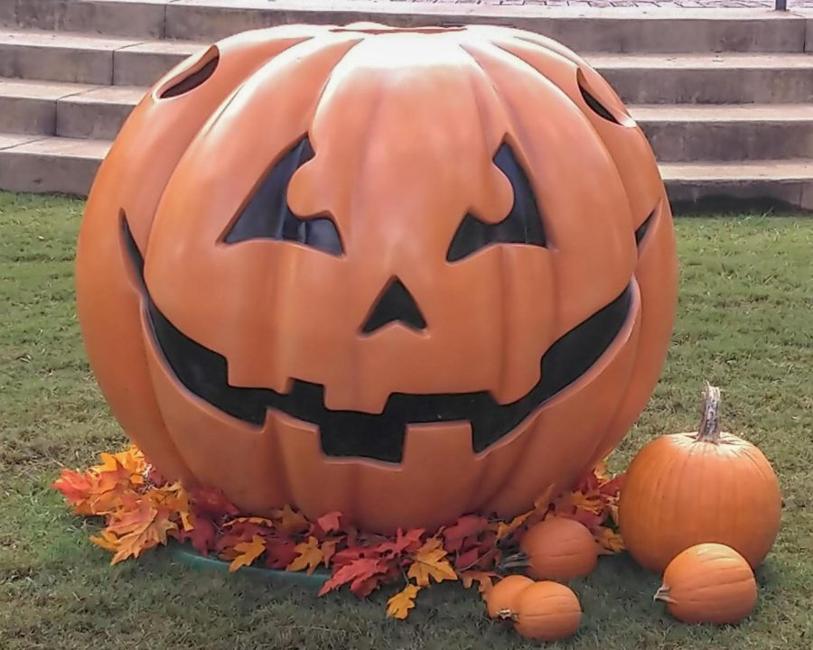 A wearable Halloween pumpkin decoration sits near the fountain in Downtown Dallas.